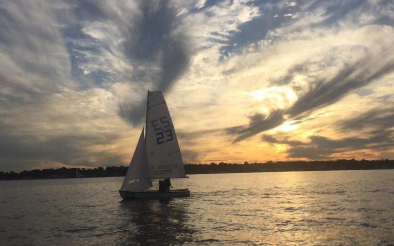 A phot of a sailboat at sunset