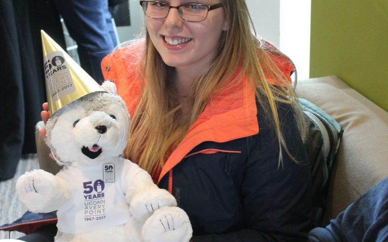 student holding stuffed husky