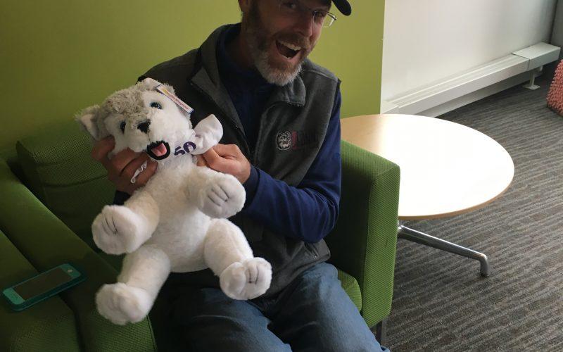 Staff holding stuffed husky