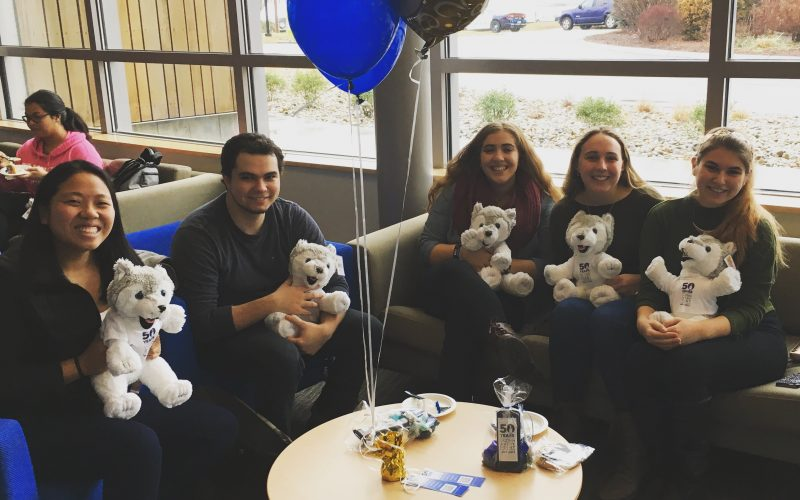 students holding stuffed huskies
